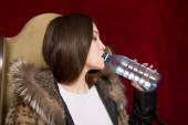 The girl in a fur jacket drinking water from a bottle — Stock Photo