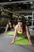 Two young women doing push-ups in the gym — Stock Photo