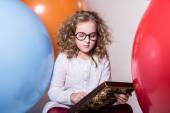 Thoughtful curly teen girl in glasses with wooden abacus on the — Stock Photo