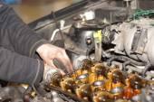 Dirty car mechanic hands examining car automobile at repair service station — Stock Photo