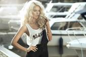Stylish woman in dungarees standing on marina — Stock Photo