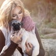 Young girl smiling in autumn scenery with pug dog — Stock Photo #59814515