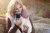Young girl smiling in autumn scenery with pug dog — Stock Photo