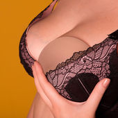 Silicone implants on bra with natural brest — Stock Photo