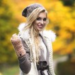 Young girl smiling in autumn scenery — Stock Photo #64226883