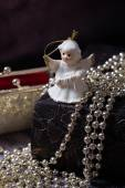 Ceramic angel standing on the old book with golden, shiny, red purse — Stock Photo