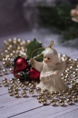 Christmas angel standing on the wood table with christmas chain — Stock Photo