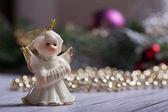Christmas angel standing on the wood table with christmas chain — Zdjęcie stockowe