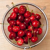 Wet cherries in stainer — Stock Photo