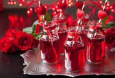 Small bottles with cranberry cocktail — Stock Photo