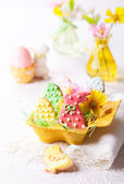 Easter cookies and flowers in vases — Stock Photo
