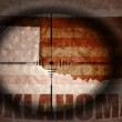 Sniper scope aimed at the vintage american flag and oklahoma state map — Stock Photo #75294991