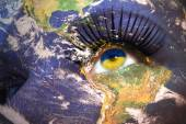 Woman's face with planet Earth texture and ukrainian flag inside the eye.  — Stock Photo