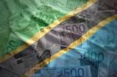 Colorful waving tanzanian flag on a euro money background — Stock Photo