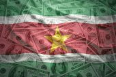 Colorful waving surinamese flag on a american dollar money background — Stock Photo