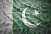 Colorful waving pakistani flag on a american dollar money background — Stock Photo