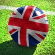 Football ball with the national flag of great britain lies on the green field near the white line — Stock Photo #79029236