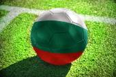 Football ball with the national flag of bulgaria lies on the green field near the white line — Stock Photo