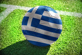 Football ball with the national flag of greece lies on the green field near the white line — Stock Photo