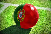 Football ball with the national flag of portugal lies on the green field near the white line — Stock Photo