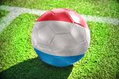 Football ball with the national flag of Luxembourg on the field — Stock Photo