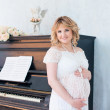 Pregnant woman near the piano. Music for the baby. — Stock Photo #52491261