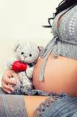 Close up of pregnant belly. Woman expecting a baby with a cute teddy bear. — Stockfoto