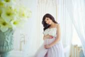 Sanfte schwangerschaft. schön schwanger in hellen weißen kleid mit orchideen — Stockfoto