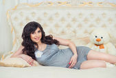 Tender pregnant in gray dress on the bed  hugging tummy — 图库照片