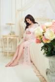 Bella ragazza incinta in una vestaglia di pizzo seduto su un letto di rose — Foto Stock