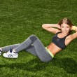 Athletic young woman doing exercises for abdominal muscles on  outdoors — Stock Photo #69147893