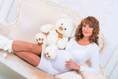 Redheaded pregnant girl in a knitted dress with teddy bear on the couch — Stock Photo