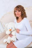 Close-up pregnant girl in knit dress with teddy bear — Stock Photo