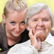 Senior woman with her caregiver. Happy and smiling. — Stock Photo #57985169