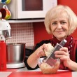 Mature woman cooks peeling apple in red kitchen.  — Stock Photo #57985203
