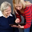Young woman learns older woman how to use tablet. — Stock Photo #57985253