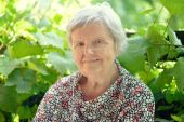 Senior woman smiling and dreaming in garden. — Stock Photo