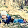 Little girl lying on grass in forest — Stock Photo #70779819