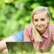 Young attractive woman lying on lawn with laptop. — Stock Photo #70779987