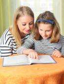 Happy girl and grandmother studying — Stock Photo
