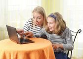 Girl and grandmother using a laptop in home — Stock Photo