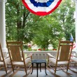Four wooden rocking chairs and the American flag — Stock Photo #67755799