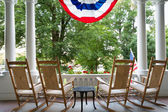 Four wooden rocking chairs and the American flag — Stock Photo