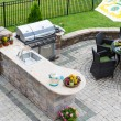 Outdoor kitchen and dining table on a paved patio — Stock Photo #67886151