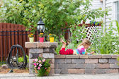 Cute little girl playing on a garden wall — Stock Photo