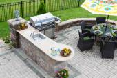 Outdoor kitchen and dining table on a paved patio — Stock Photo