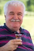 Smiling senior man enjoying a glass of tea — Stock Photo