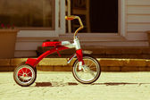 Child's rusted red tricycle standing ready — Stock Photo