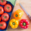 Tomatoes and Bell Peppers on Top of Chopping Board — Stock Photo #69908159