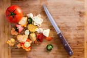 Organic Wastes on Wooden Chopping Board with Knife — Stock Photo